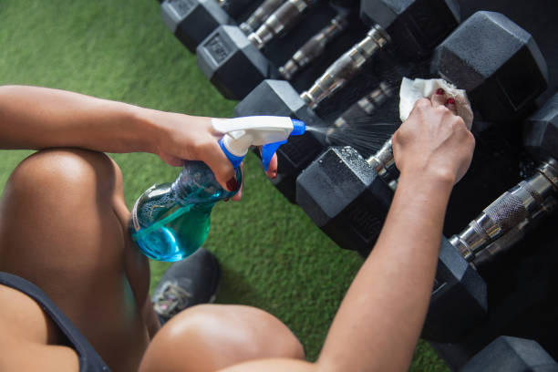 Clean and sanitize fitness equipment with disinfectant spray stock photo