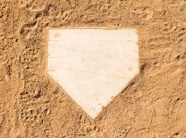 Clean baseball home plate set in dirt stock photo
