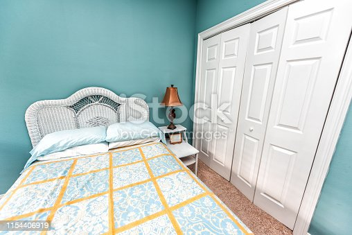 Clean bed linen with headboard nightstand table and lamp with vintage beach theme decorative blue green pillows in bedroom in staging model home house by closet