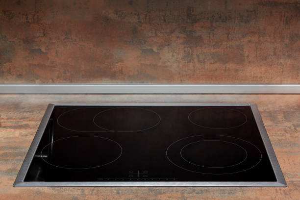 Clean black surface of an electric cooker built into the kitchen worktop stock photo