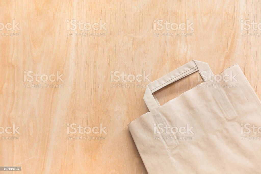 Clean brown kraft paper bag lying on a plywood table. stock photo