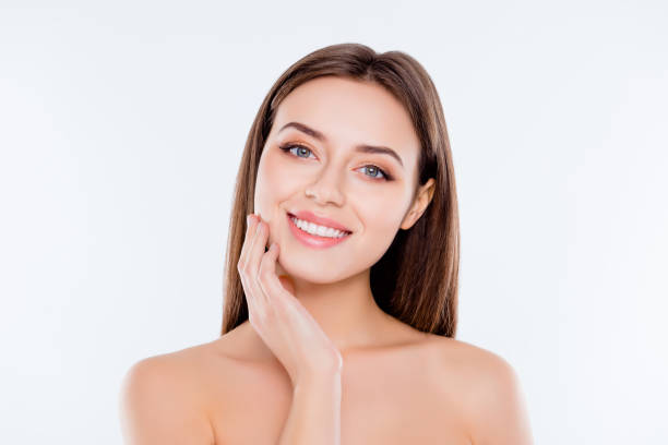 clean clear pampering wellness freshness rejuvenation concept. close up portrait of beautiful tender cute pure girl touching her smooth soft flawless perfect skin on cheek isolated on white background - gładki zdjęcia i obrazy z banku zdjęć