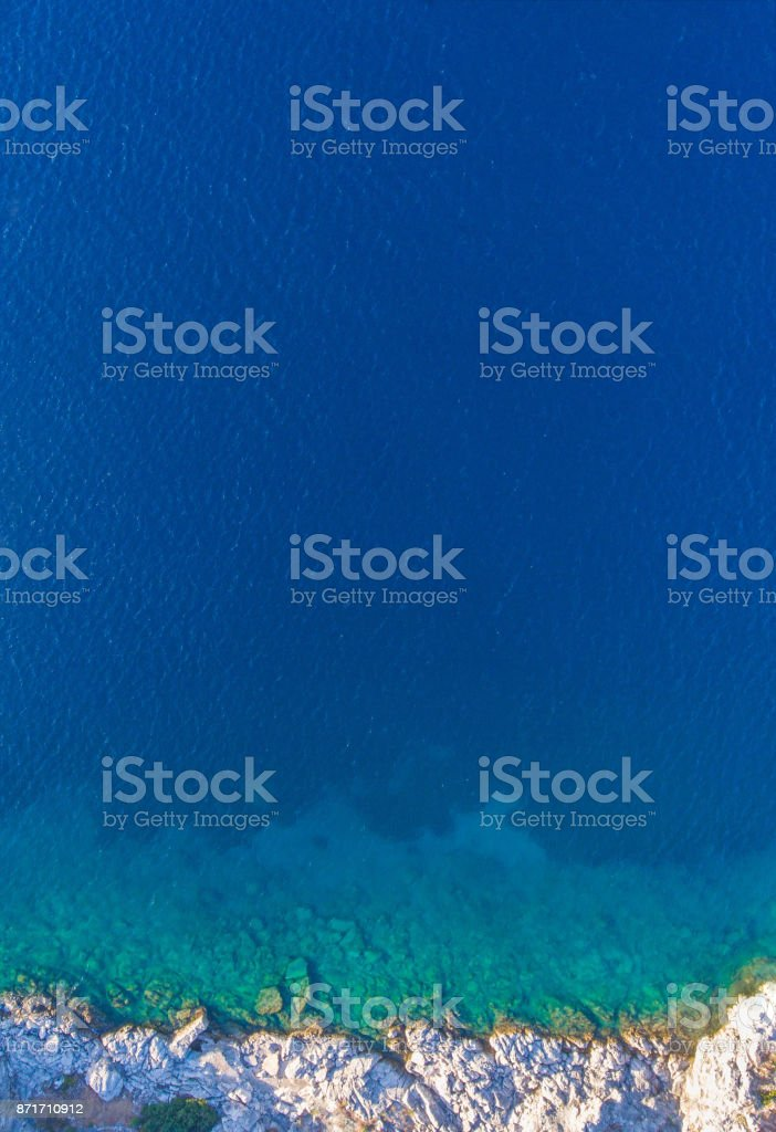Clean clear water is bordered with rocks on the shore. Aerial view. stock photo