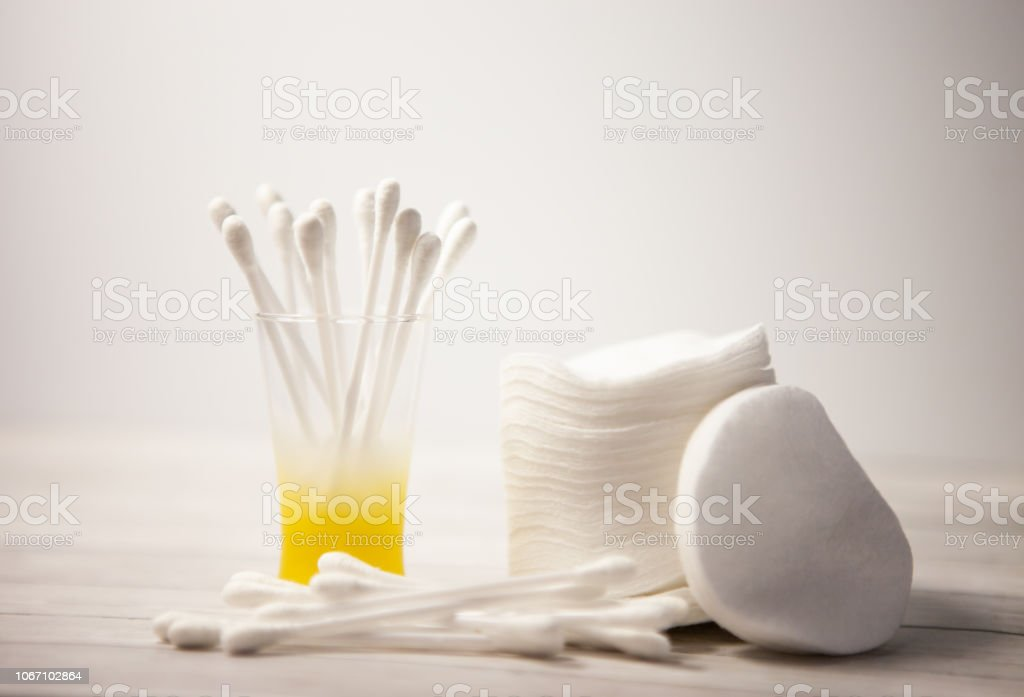Clean cotton pads and sticks in a glass for the body on a light...