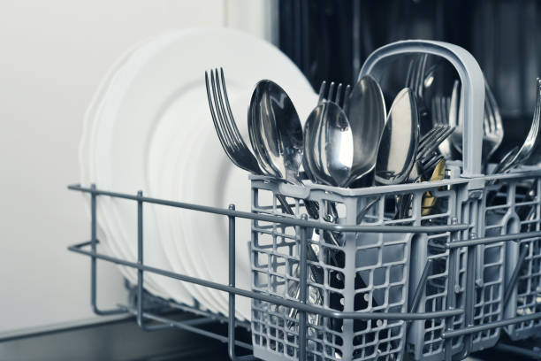 Clean cutlery and plates Clean cutlery and plates after washing in dishwasher machine dishwasher stock pictures, royalty-free photos & images