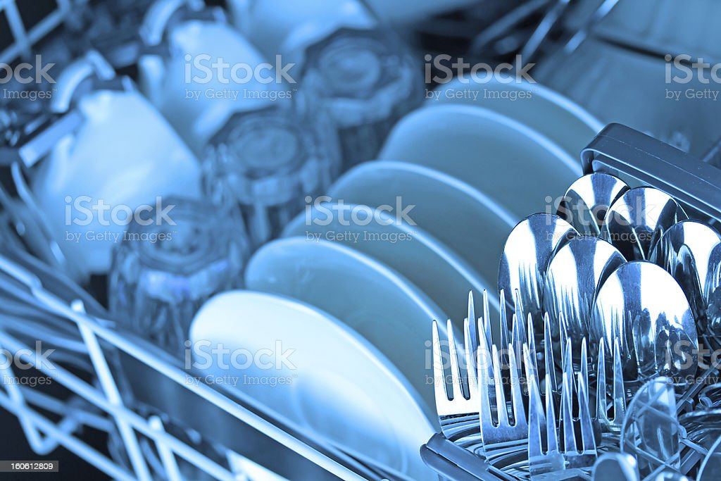 Clean dishware neatly organized in a dishwasher rack stock photo