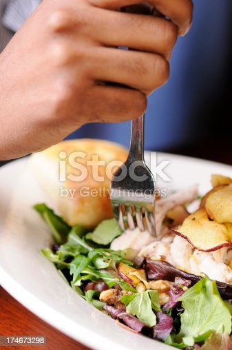 A woman's hand is digging into a healthy chicken salad.