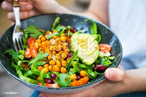 Clean eating, vegan healthy salad bowl , woman holding salad bowl, plant based healthy diet with greens, salad, chickpeas and vegetables