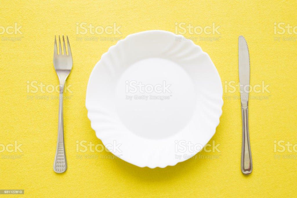 Temiz, boş, beyaz tabak, çatal ve bıçak ile bir tablo üzerinde sarı masa örtüsü. Çatal bıçak takımı kavram. Düz yatıyordu. Üstten Görünüm. - Royalty-free Acıkmış Stok görsel