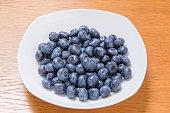 Clean freshly picked blueberries on white plate - close up studio shot. ( Ingredients:  Antioxidants , Vitamin C, Antioxidant)