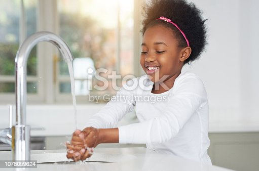 Shot of an adorable little girl washing her hands