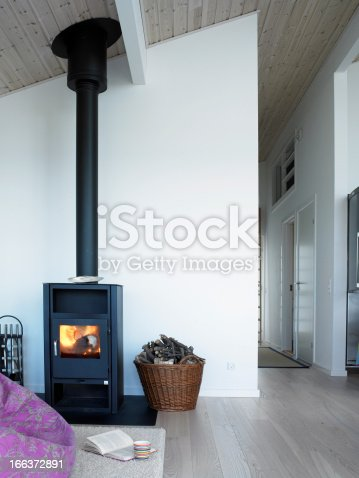 In the light room the wood stove is placed with a fluffy carpet in front, where you can sit down and enjoy the cosiness with a book in the illumination of the flames.