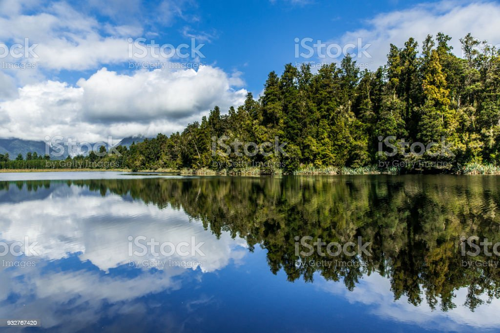 Clean lake mirroring blue sky and green trees Clean lake mirroring blue sky and green trees Beauty Stock Photo