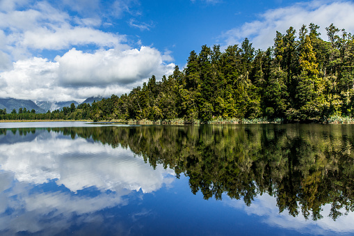 Clean Lake Mirroring Blue Sky And Green Trees Stock Photo - Download Image Now