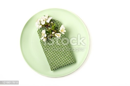 1136239089 istock photo Clean plate on a light background. Branch of blooming cherry and a napkin on a plate. Top view. 1219517815