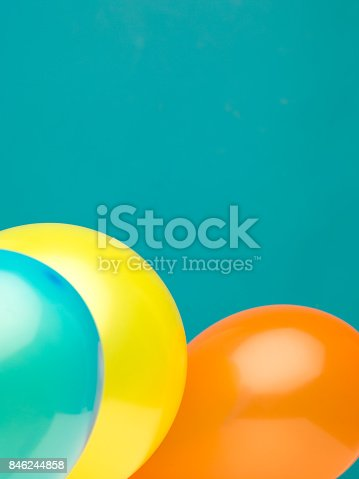 istock clean portrait composition made from three balloons aquamarine, yellow, and orange against a cyan background 846244858