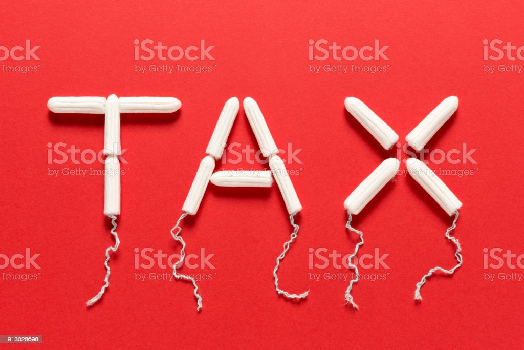 Clean Tampons Forming the Word TAX on a Red Background stock photo