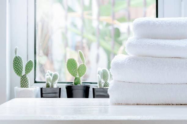 Limpie la toalla en la mesa blanca cerca del alféizar de la ventana. - foto de stock