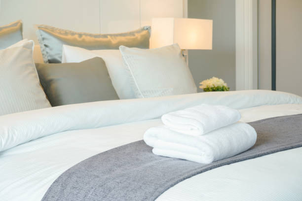 Clean towels on bed at hotel room stock photo