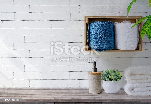 istock Clean towels with soap dispenser on shelf and wooden table in bathroom, white brick wall background. 1162161951