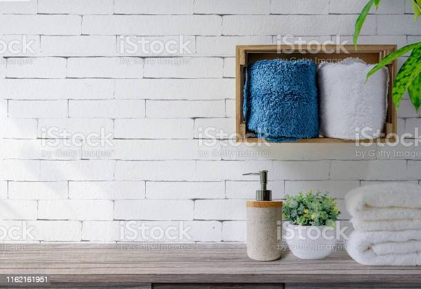 Clean towels with soap dispenser on shelf and wooden table in white picture id1162161951?b=1&k=6&m=1162161951&s=612x612&h=emqmrqgj67fnzacgwws1ihjozxvcrazl9rux4nmsfga=