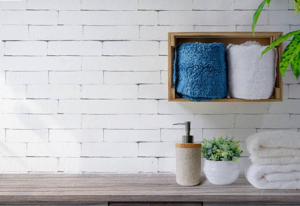 Limpie las toallas con dispensador de jabón en el estante y mesa de madera en el baño, fondo de pared de ladrillo blanco. - foto de stock