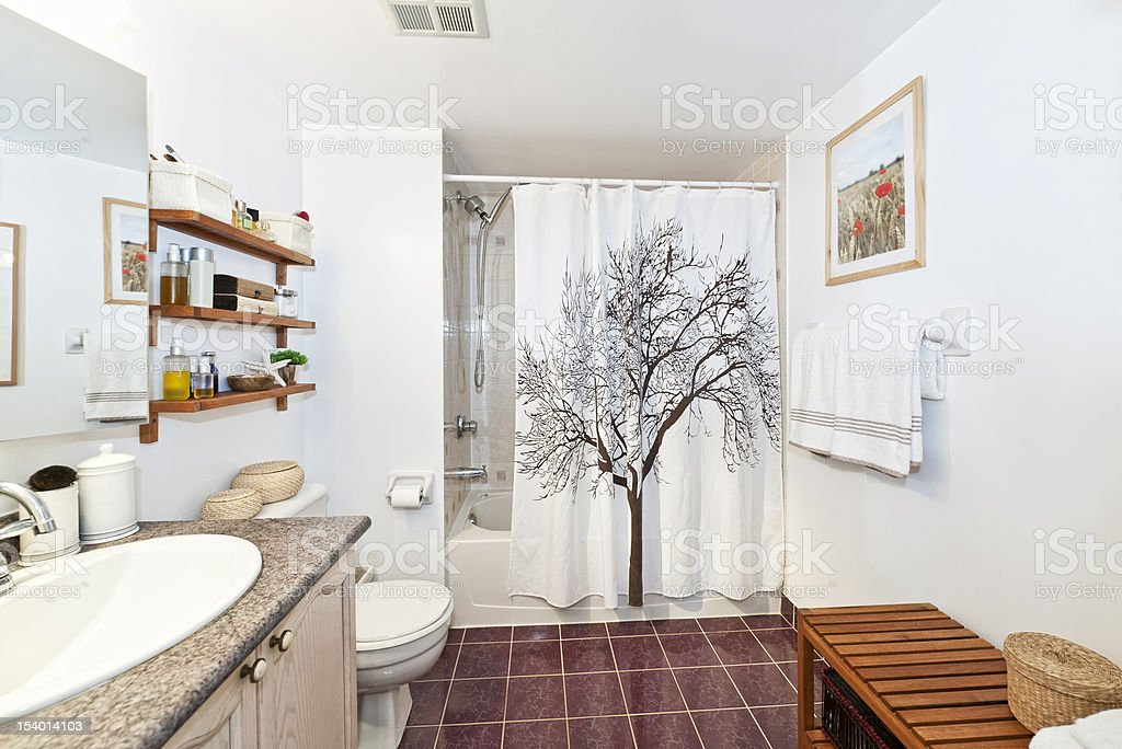 Clean white bathroom with red floors and wood accents stock photo