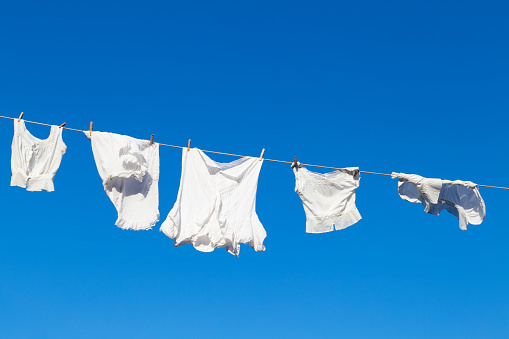 Clean white laundry drying in the sun