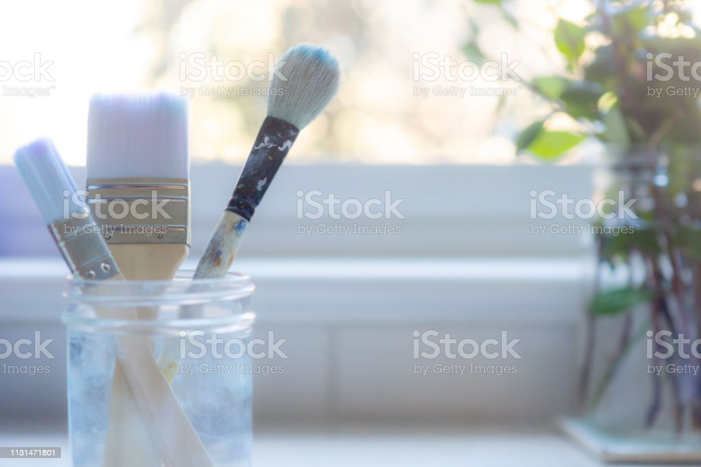 Cleaned Paint Brushes on Kitchen Counter in front of window with plants stock photo