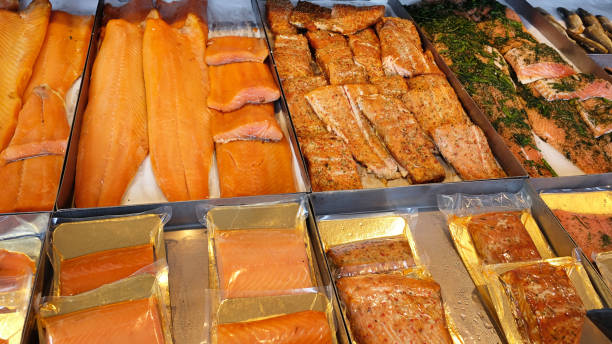 cleaned smoked and spiced norwegian salmon individually packed and un-packed, at a fish market in bergen, norway. - banchi di pesci foto e immagini stock