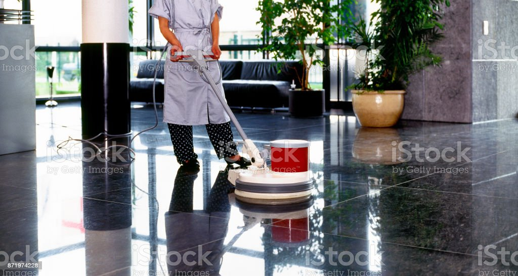 Adult cleaner maid woman with uniform cleaning corridor pass floor
