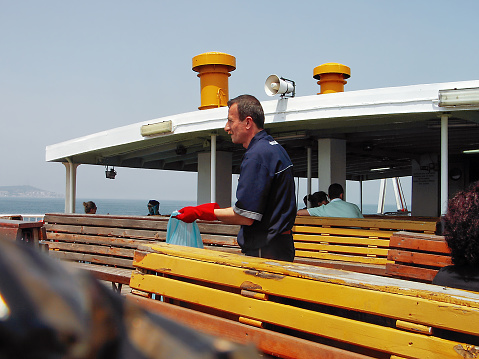 Istanbul, Turkey - September 22, 2005: a male person from deck crew looking around to find and clean garbage on top floor of Marmara Sea passenger ship in a clear air in a summer day