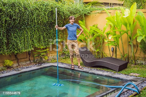 Cleaner of the swimming pool . Man in a blue shirt with cleaning equipment for swimming pools. Pool cleaning services.