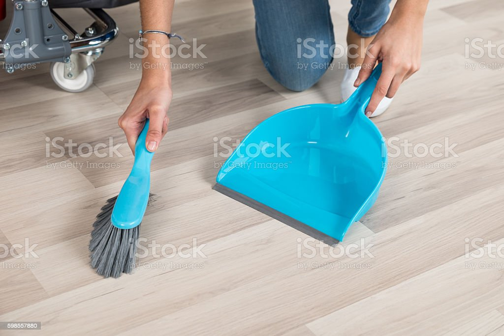 Cleaner Sweeping Floor With Broom And Dustpan In Office stock photo