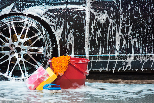 Bucket with sponges and brush with lots of foam next to car tire.