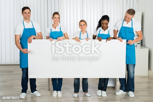 1159989540 istock photo Cleaners Holding Banner In Office 625879072