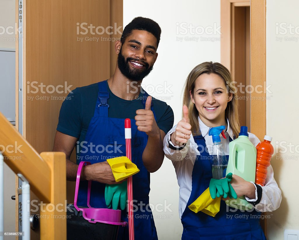 cleaners in uniform cleaners standing at house doorway stock photo