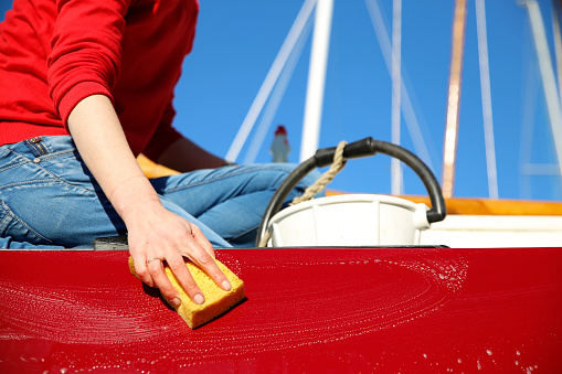 A young woman cleaning a classic sailing boat