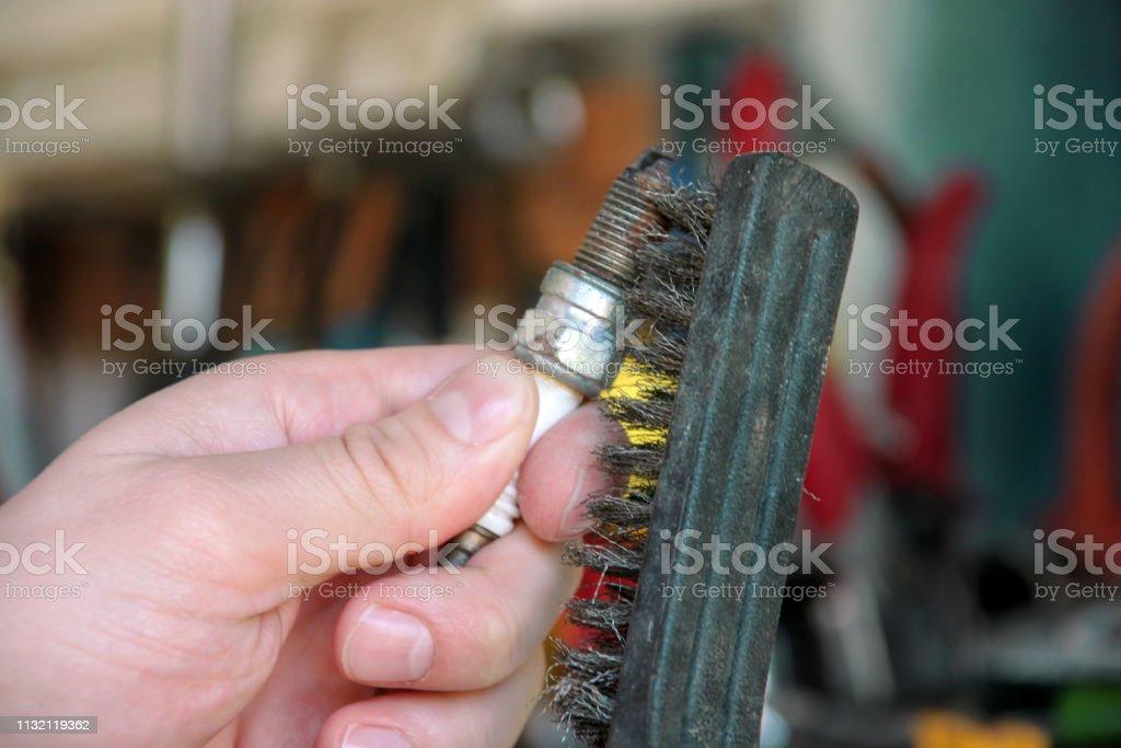 Limpando um plugue de faísca do motor de carro com escova do fio na garagem do carro. O mecânico está escovando a vela de ignição usada com uma escova do aço inoxidável na auto oficina dos mecânicos. Trabalhador com as ferramentas de serviço à di - foto de acervo