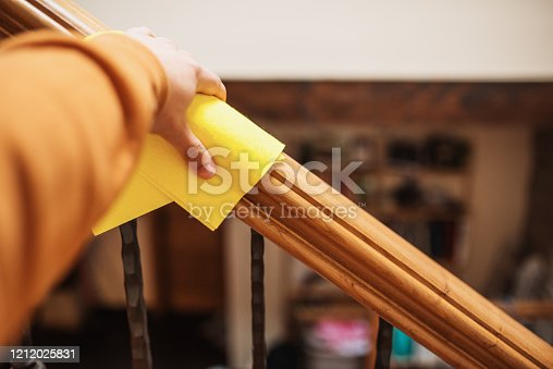 A human hand cleaning a railing