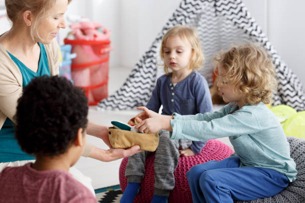 Cleaning after play Little kids and their teacher cleaning toys after play kids cleaning up toys stock pictures, royalty-free photos & images