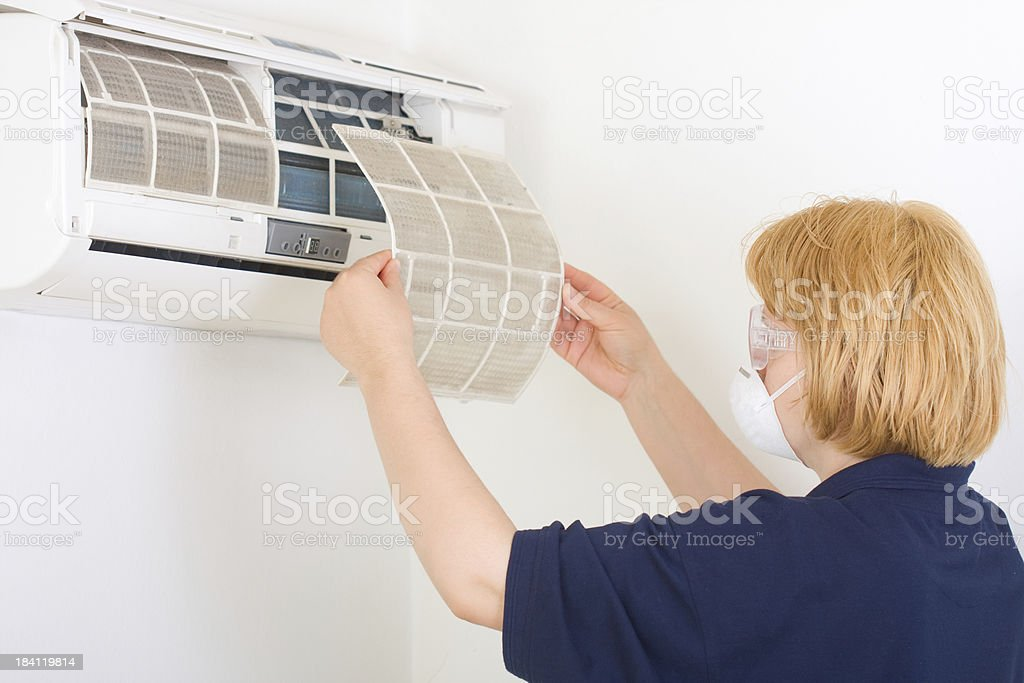 Cleaning air conditioner from dust stock photo