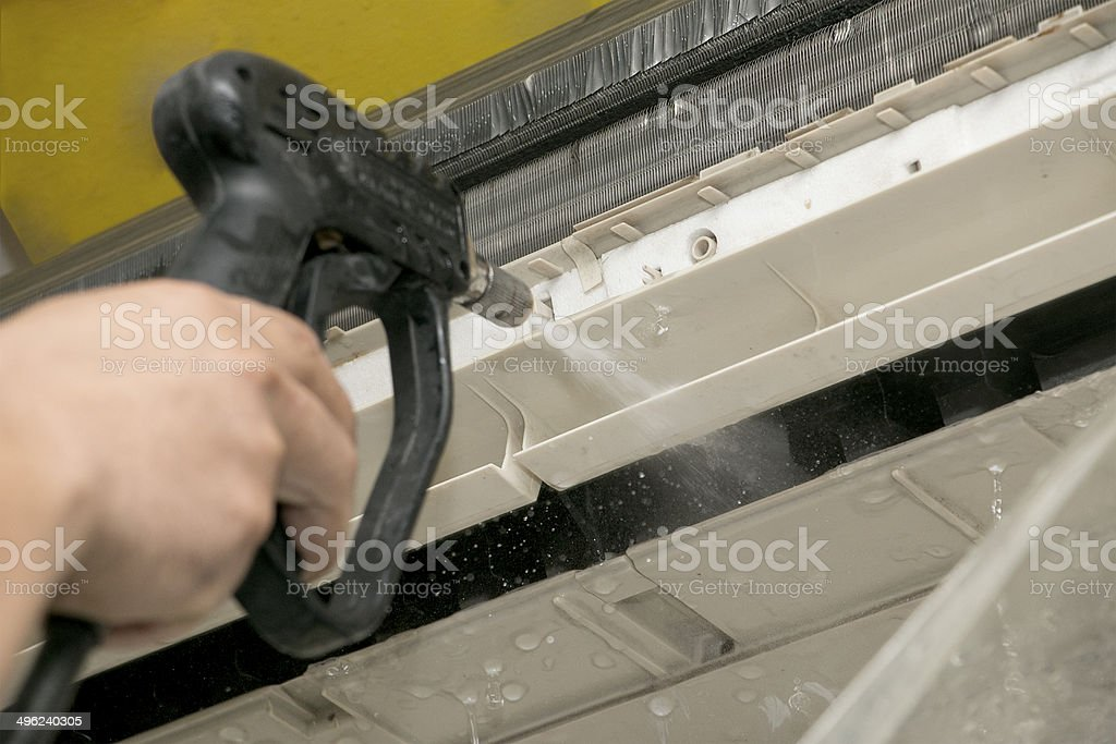 Cleaning air-conditioner with washing machine stock photo