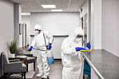 Two people in protective workwear cleaning and disinfecting offices.