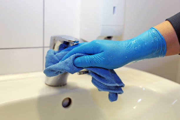 Cleaning and disinfection of a wash basin stock photo