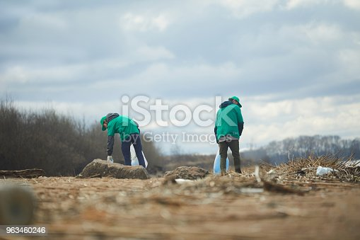 Two active greenpeacers working on littered abandoned territory somewhere in the outskirts