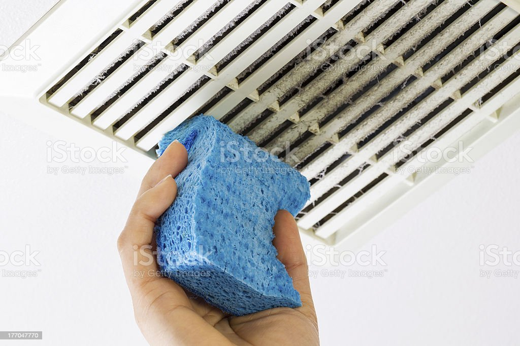 Cleaning Bathroom Fan Vent Cover with Sponge stock photo
