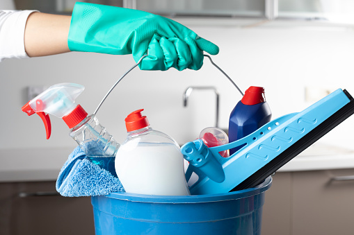 Woman holding cleaning products with glove.