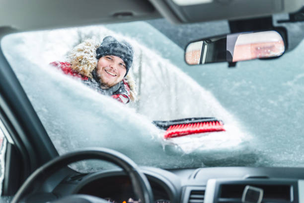 cleaning car after snow storm smiling man with brush view from inside interior stock photo