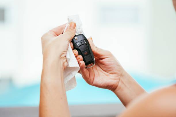 Reinigung der Autoschlüssel, um eine Kontamination des Coronavirus zu verhindern. Vorsichtsmaßnahme gegen Covid-19 – Foto